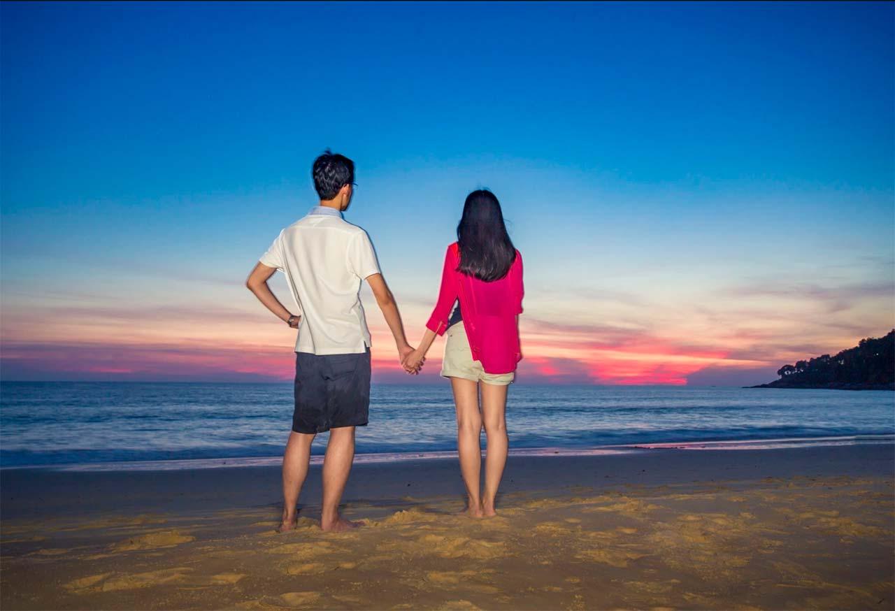 Pareja de novios disfrutan del atardecer en playa de Tailandia