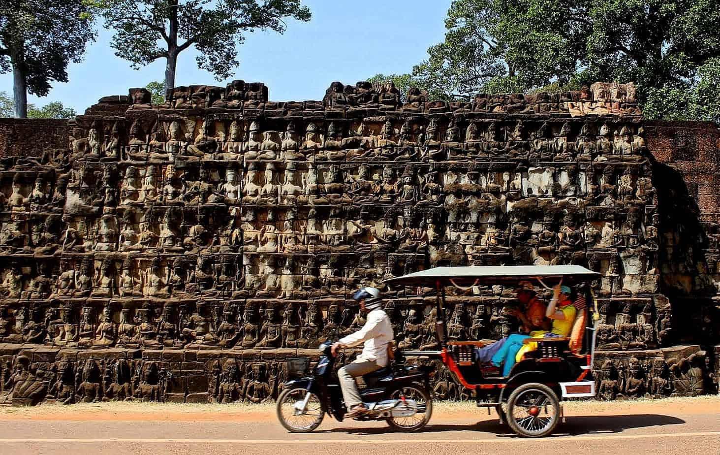 Imagen de dos turistas visitando los Templos de Angkor sobre un tuc tuc