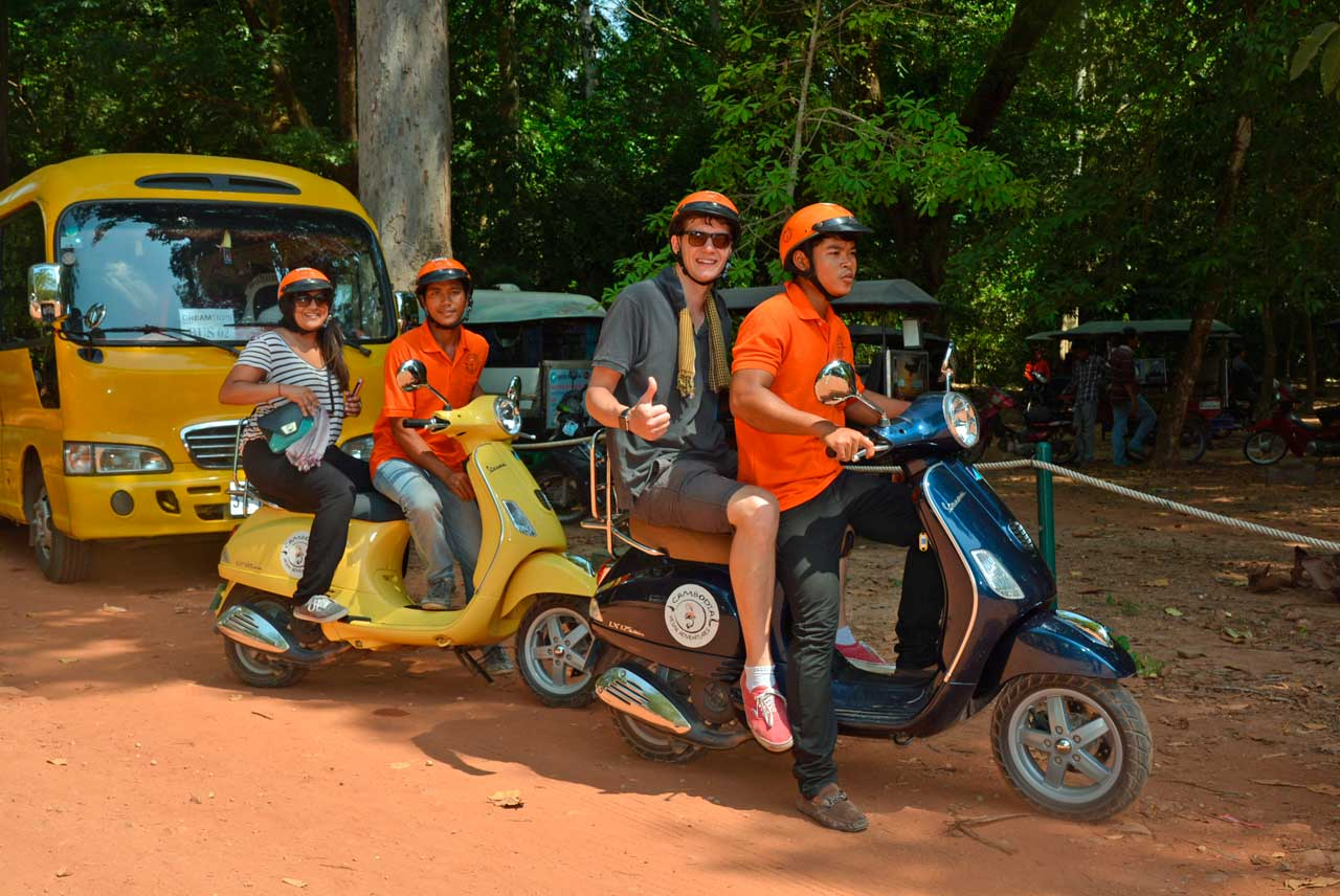 Imagen de turistas en una moto vespa con guía